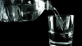 Relleno de un vidrio de consumición de agua con las burbujas con la botella en fondo negro, el tiro en la cámara lenta, la nutric almacen de metraje de vídeo