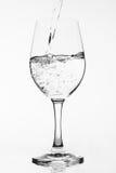 Relleno de un vidrio puro de agua en el fondo blanco Fotos de archivo libres de regalías