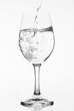 Relleno de un vidrio puro de agua en el fondo blanco Imagen de archivo