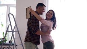Relocalización feliz, abrazos del hombre y hembra que circunda en brazos durante la renovación casera al plano metrajes