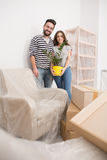 Relocating, yong couple standing in new apartment with furniture coverd with foil. Royalty Free Stock Image