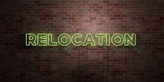 RELOCATION - fluorescent Neon tube Sign on brickwork - Front view - 3D rendered royalty free stock picture. Can be used for online banner ads and direct Royalty Free Stock Photo