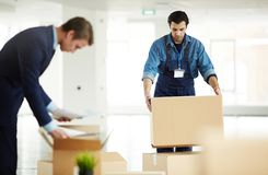 Help with relocation. Relocation service worker putting packed box on top of another one while helping to carry packages Royalty Free Stock Images