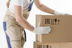 Relocation services concept. Mover`s hands In uniform carrying cardboard Box. Loader puts cardboard boxes royalty free stock photo