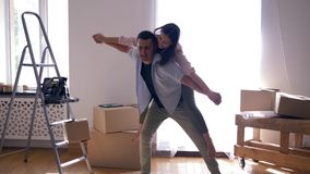 Relocation to new housing, joy pair is laughing and guy is Carrying girl on back among boxes during moving to apartment. Relocation to new housing, joy pair is stock video footage
