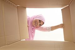 Relocation. Woman opening a carton box and looking inside, relocation and unpacking concept Stock Photo