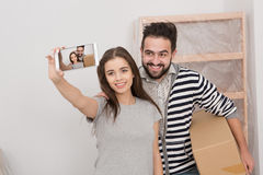Relocation young happy couple making selfie shot in their new apartment. Stock Photography