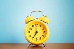 Reloj amarillo del ` del despertador siete o por la mañana en la tabla contra la pared azul fotografía de archivo libre de regalías