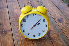 Reloj amarillo en la tabla de madera vieja fotografía de archivo libre de regalías