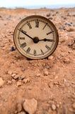 Reloj análogo clásico en la arena Foto de archivo