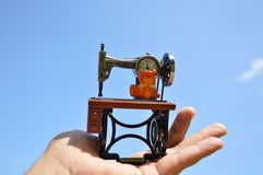 Reloj Antic de la máquina de coser en la palma con el cielo azul fotografía de archivo libre de regalías