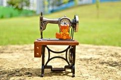 Reloj Antic de la máquina de coser en una tabla imagenes de archivo