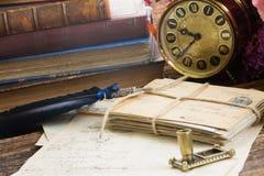Reloj antiguo con la pila de correo Imágenes de archivo libres de regalías
