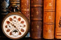Reloj antiguo con los libros antiguos Fotos de archivo