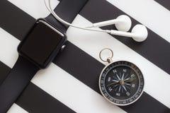 Reloj, auriculares y compás en un fondo blanco y negro Imágenes de archivo libres de regalías
