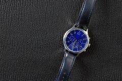 Reloj azul con la correa de cuero sobre el cuero modelado negro del lagarto imagen de archivo libre de regalías