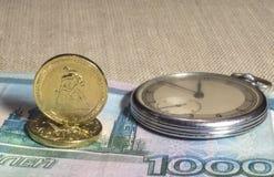 Reloj, billetes de banco y monedas retros Fotografía de archivo libre de regalías