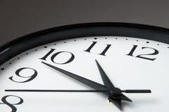 Reloj blanco con la frontera negra en fondo gris fotos de archivo
