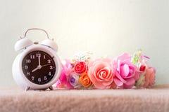 Reloj blanco con las flores en una tabla en estilo retro del vintage silenciado Foto de archivo libre de regalías