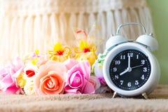 Reloj blanco con las flores en una tabla en estilo retro del vintage silenciado Imágenes de archivo libres de regalías