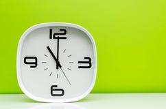 Reloj blanco en fondo verde claro Fotos de archivo libres de regalías