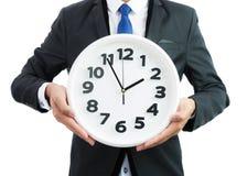 Reloj blanco que se sostiene en manos del hombre de negocios aislado foto de archivo