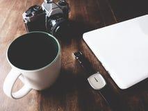 Reloj, cámara, de cerámica, ordenador portátil en la tabla de madera fotos de archivo