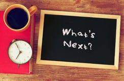 ¿Reloj, café, y blackboad con la frase cuál es siguiente? escrito en él Imagen de archivo