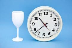 Reloj-cara blanca del dial de reloj con las flechas negras y taza en azul Imagenes de archivo