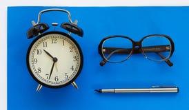 Reloj clásico del escritorio, pluma, vidrios en un fondo azul Fotos de archivo libres de regalías