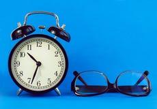 Reloj clásico del escritorio, vidrios en un fondo azul Imagen de archivo libre de regalías