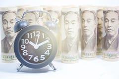 Reloj clásico en el rollo de Yen Banknote, del concepto y de la idea del tiempo foto de archivo libre de regalías