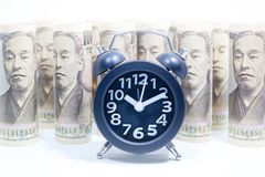 Reloj clásico en el rollo de Yen Banknote, del concepto y de la idea del tiempo fotografía de archivo libre de regalías