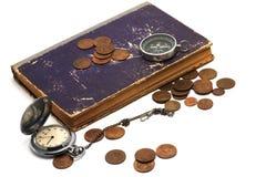 Reloj, compás, libro y monedas viejos Fotos de archivo
