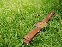 Reloj con el fondo de la hierba Imagenes de archivo