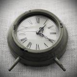 Reloj con el fondo de la lona Imagenes de archivo