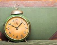 Reloj con el libro viejo en fondo Foto de archivo libre de regalías