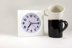 Reloj con la taza de los pares en backgound Imagenes de archivo