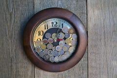 Reloj con las monedas Imagenes de archivo