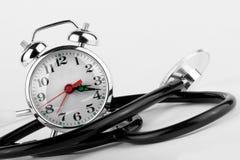 Reloj de alarma con el estetoscopio Imágenes de archivo libres de regalías