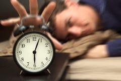 Reloj de alarma con el modelo masculino en cama en fondo. Imagen de archivo libre de regalías