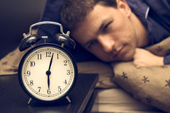Reloj de alarma con el modelo masculino en cama en fondo. imagen de archivo