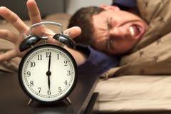 Reloj de alarma con el modelo masculino en cama en fondo. Imagenes de archivo