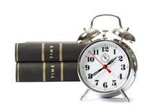 Reloj de alarma con los libros fotos de archivo