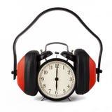 Reloj de alarma con los protectores contra el ruido encendido. Foto de archivo libre de regalías