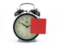 Reloj de alarma con una etiqueta Fotos de archivo libres de regalías