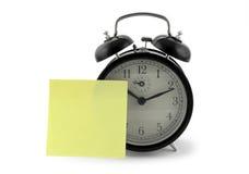 Reloj de alarma con una nota Imagen de archivo libre de regalías