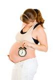 Reloj de alarma de la explotación agrícola de la mujer embarazada cerca de su vientre Fotografía de archivo libre de regalías