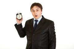 Reloj de alarma de la explotación agrícola del hombre de negocios. Concepto perdido del tiempo Foto de archivo libre de regalías