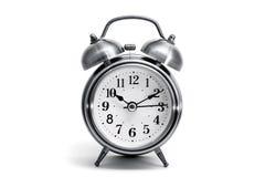 Reloj de alarma de la vendimia en el fondo blanco Fotos de archivo libres de regalías